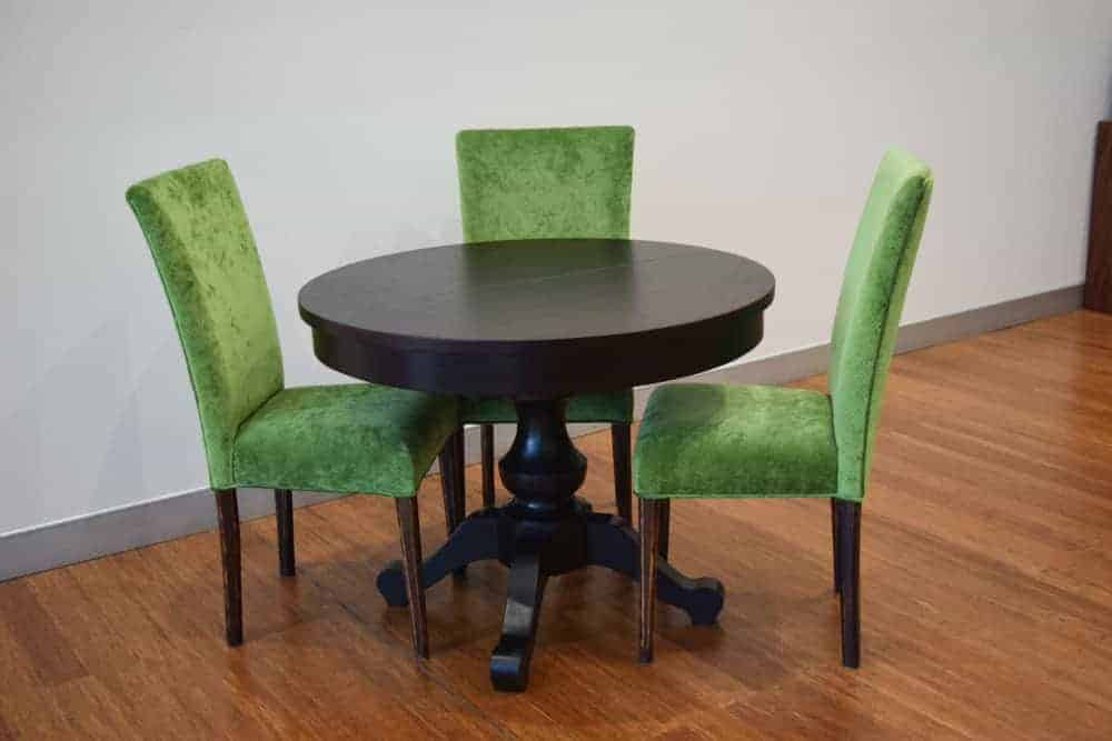 American Oak Round dining table stained black with our Kingston high back dining chair in an emerald green velvet.